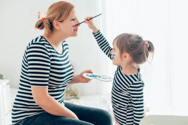 Mom and daughter spending time together at home, little girl painting