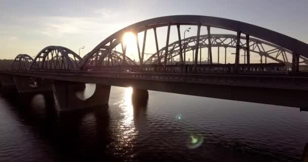 Vlak jede na krásném mostě při západu slunce. Zadní světlo. Siluet. Letecká fotografie