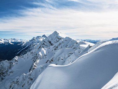 Panoramic view of Aibga mountain ridge with Stone Pillar Peak in Rosa Khutor alpine resort at sunny winter day. Sochi, Russia