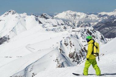 Snowboarder standing at panoramic background of Caucasus Aibga mountain ridge in Russia
