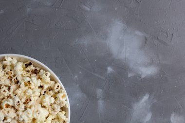 Popcorn in white bowl on grey table. Top view with copy space