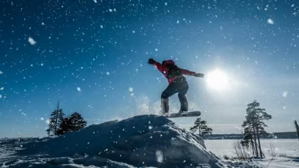 Kinotag. Anfänger-Snowboarder im Sprung mit einem leichten Schnee-Sprungbrett, Winterlandschaft, Videoschleife