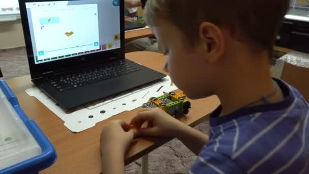 Piccolo bambino che gioca con i blocchi colorati piccoli di un costruttore.