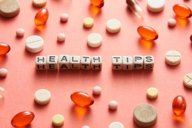 Black and white title HEALTH TIPS from white cubes on the table with tablets on coral background