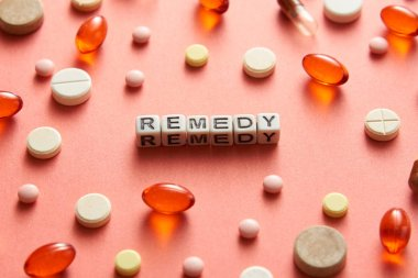 Black and white title REMEDY from white cubes on the table with tablets on coral background