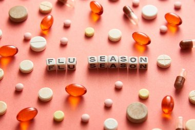 Black and white title FLU SEASON from white cubes on the table with tablets on coral background