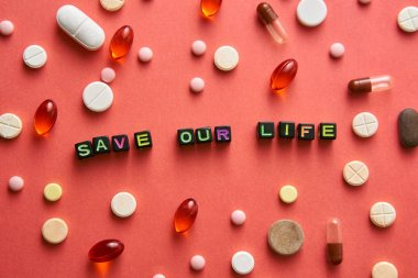 Multicolored title SAVE OUR LIFE from black cubes on the table with tablets on coral background