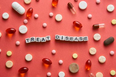 Black-and-white title TREAT DISEASE from white cubes on the table with tablets on coral background