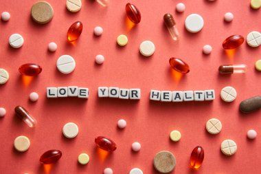 Black and white title LOVE YOUR HEALTH from white cubes on the table with tablets on coral background