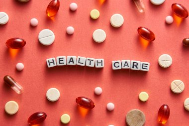 Black and white title HEALTH CARE from white cubes on the table with tablets on coral background