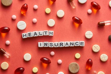 Black and white title HEALTH INSURANCE from white cubes on the table with tablets on coral background