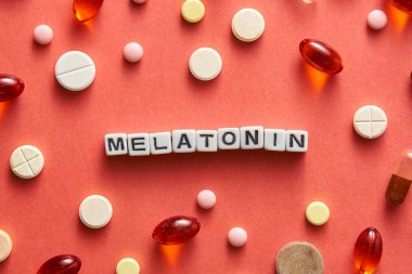 Black and white title MELATONIN from white cubes on the table with tablets on coral background