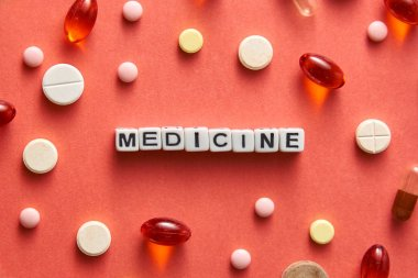 Black and white title MEDICINE from white cubes on the table with tablets on coral background