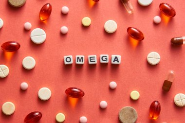 Black and white title OMEGA from white cubes on the table with tablets on coral background