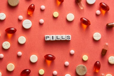 Black and white title PILLS from white cubes on the table with tablets on coral background
