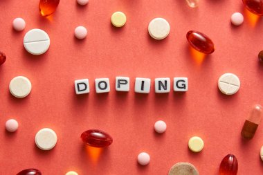 Black and white title DOPING from white cubes on the table with tablets on coral background