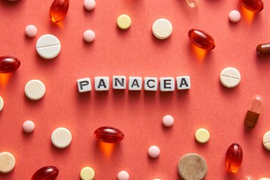 Black and white title PANACEA from white cubes on the table with tablets on coral background