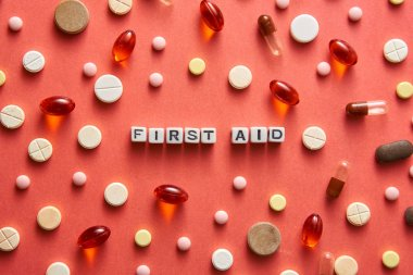 Black and white title FIRST AID from white cubes on the table with tablets on coral background