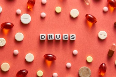 Black and white title DRUGS from white cubes on the table with tablets on coral background