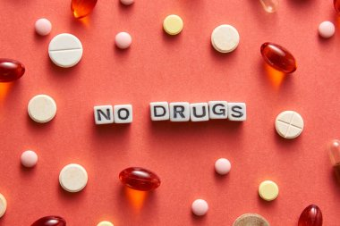 Black and white title NO DRUGS from white cubes on the table with tablets on coral background
