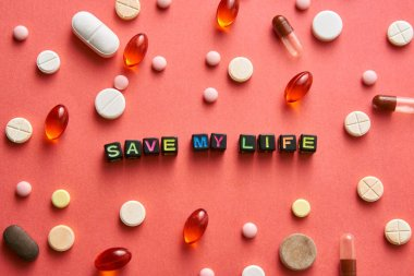 Multicolored title SAVE MY LIFE from black cubes on the table with tablets on coral background