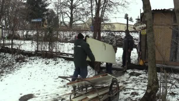 Olomouc, Česká republika, 30 ledna 2018: Bezdomovci starší muži se přepravě prkna a dveře dát na zem, v zimě a sněhu. Velmi autentické, který ukazuje chudoba chudých, Evropa