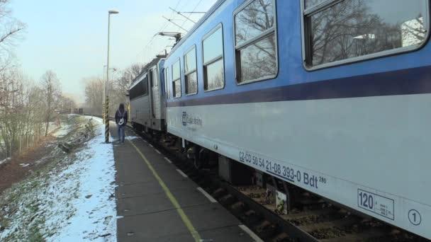 Olomouc, Česká republika, 29 ledna 2018: Osobní vlak odjíždí ze stanice v zimě, muž procházky po kolejích nebezpečné pro život, Česká republika, Evropa, Evropská unie
