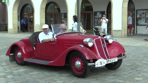 OLOMOUC, CZECH REPUBLIC, JULY 5, 2018: Historic cars veterans on a public car ride through city of Olomouc drive people, first arriving of Tatra 75 T 87 1940, Europe