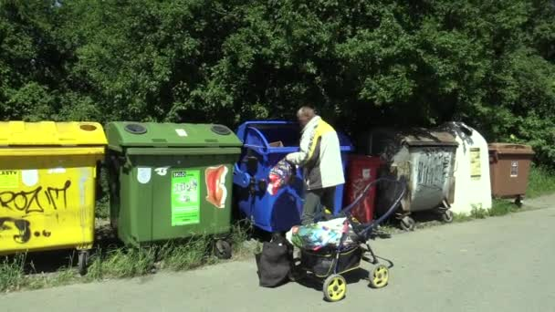 OLOMOUC, CZECH REPUBLIC, MAY 5, 2018: The homeless poor chooses a dustbin paper container bin garbage, very authentic and real, city street life, bags with a cart carriage, struggle to survive