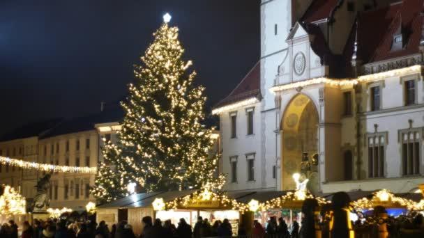 Vánoční stromeček svítící a svítí krásné zdobené zlatými ornamenty a baněk, historické architektury města Olomouc s gotickou radnicí s orlojem náměstí