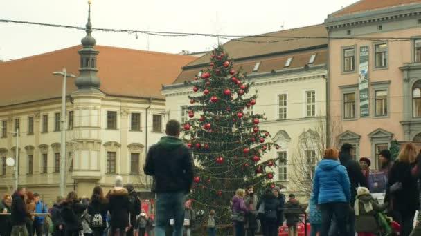 brno, Tschechische Republik, 21. Dezember 2018: Weihnachtsbaum leuchtet und leuchtet schön geschmückt mit goldenen Ornamenten und Kolben rot groß, Menschen und Zeugen Jehovas und ihre Bücher