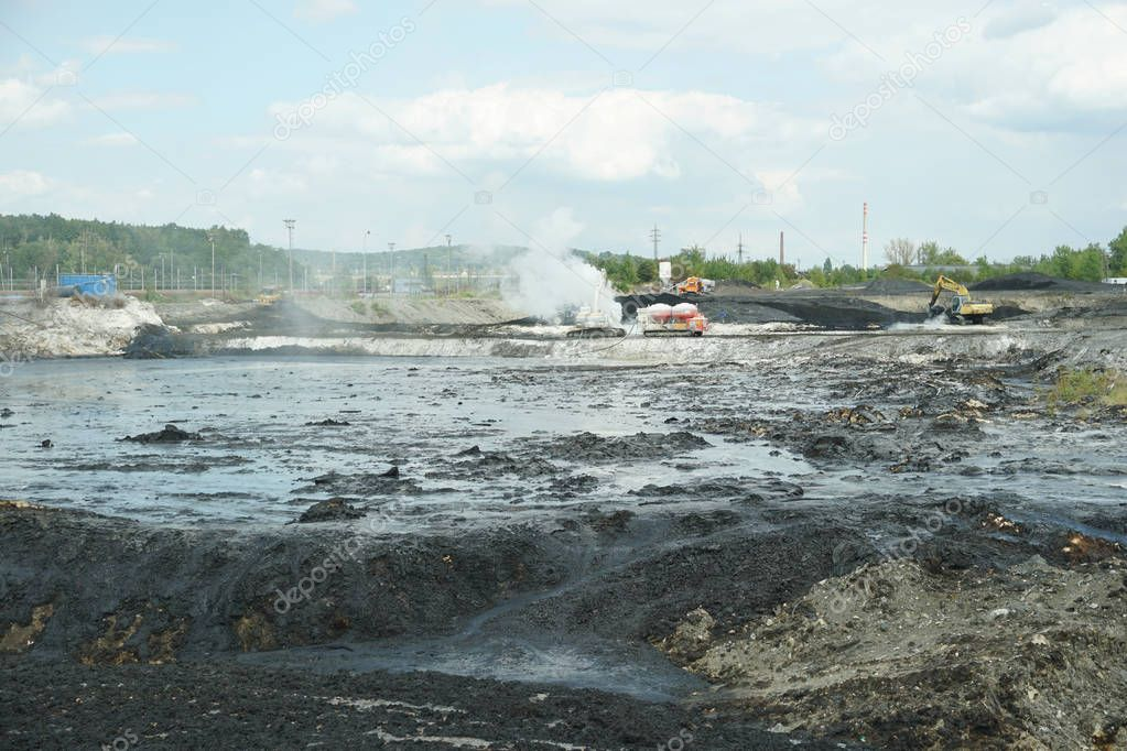OSTRAVA, CZECH REPUBLIC, AUGUST 28, 2018: Oil pollution liquidation toxic waste of remediation poisoned pollutants, excavator and chemical reaction