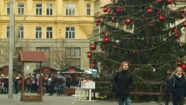 brno, Tschechische Republik, 21. Dezember 2018: Weihnachtsbaum leuchtet und leuchtet mit goldenen Ornamenten und Kolben rote große Weihnachtskugel, Zeitraffer-Menschen und Kinder am hölzernen Glockenturm