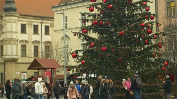 brno, Tschechische Republik, 21. Dezember 2018: Kinderschar und Weihnachtsbaum leuchten und leuchten geschmückt mit Ornamenten und Flaschen, Menschen und Kinder spazieren über den Platz