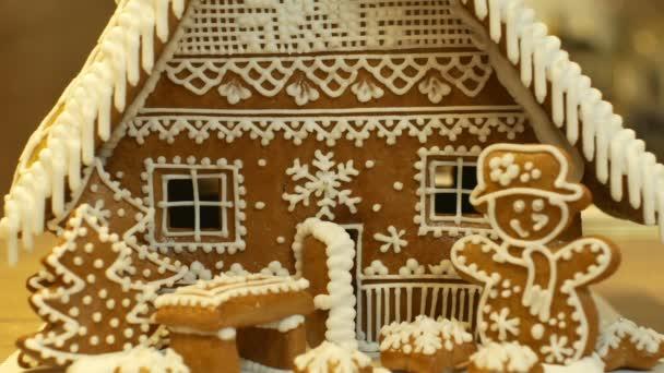 Mézeskalács ház és a ház torta gyönyörű, fa házak és a hóember, díszítik a cukrászda fehér hab a felvert tojásfehérjével, a népi kreatív munka, karácsony, télen a hó