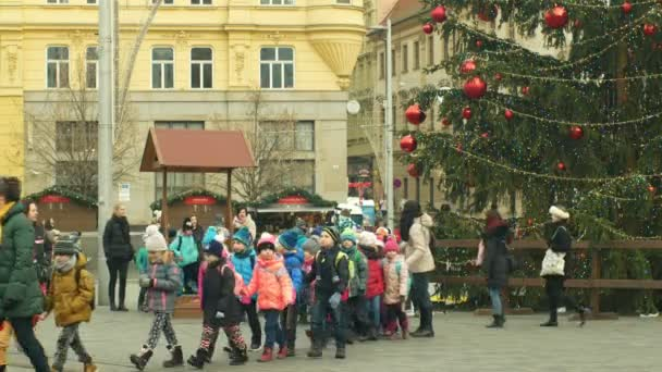 BRNO, CZECH REPUBLIC, DECEMBER 21, 2018: Christmas tree luminous and shines beautiful decorated with golden ornaments and flasks red big, childrens kindergarten goes over the road