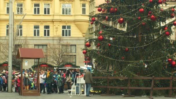 brno, Tschechische Republik, 21. Dezember 2018: Tannenbaum leuchtet und leuchtet schön geschmückt mit Ornamenten und Flaschen, Kinder am hölzernen Glockenturm, Freude am Kindergartenklingeln