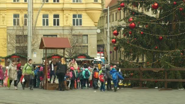 BRNO, CZECH REPUBLIC, DECEMBER 21, 2018: Christmas tree luminous and shines beautiful decorated with flasks, children at wooden bell tower, joy of kindergarten bell ring, xmas ball
