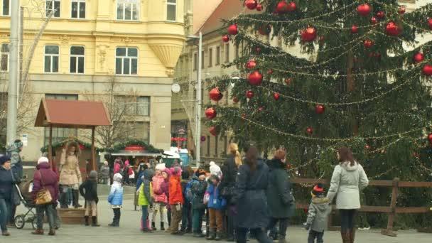 brno, Tschechische Republik, 21. Dezember 2018: Weihnachtsbaum leuchtet und leuchtet schön dekoriert mit goldenen Ornamenten und Kolben rot groß, Kinder-Kindergarten geht über die Straße, Weihnachtsball