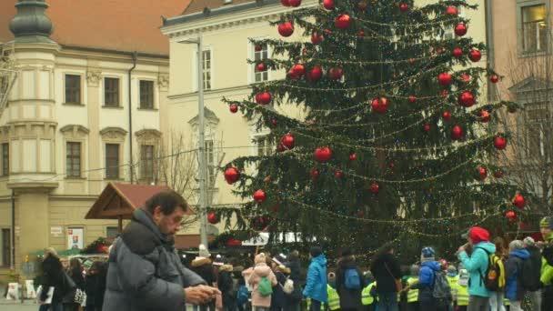 brno, Tschechische Republik, 21. Dezember 2018: Weihnachtsbaum leuchtet und leuchtet schön geschmückt mit Ornamenten und Fläschchen Weihnachtskugel, Kinder am hölzernen Glockenturm, Freude an der Kindergartenglocke