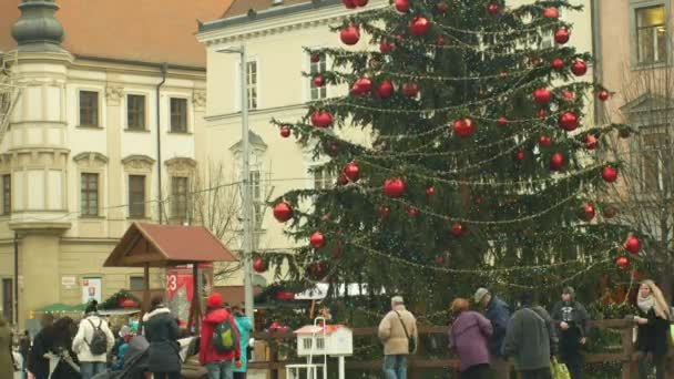 BRNO, CZECH REPUBLIC, DECEMBER 21, 2018: Christmas tree luminous and shines beautiful decorated with golden ornaments and flasks red big, time lapse people and children at the wooden bell tower