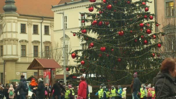 brno, Tschechische Republik, 21. Dezember 2018: Menschenkinder und Christbaum leuchten und glänzen mit Ornamenten und Fläschchen Weihnachtskugel, Kinder am hölzernen Glockenturm, Freude am Kindergartenklingeln
