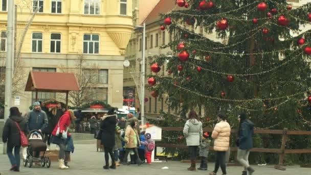 brno, Tschechische Republik, 21. Dezember 2018: Weihnachtsbaum leuchtet und leuchtet schön geschmückte Flaschen rote Weihnachtskugel, Menschen Familie Vater und Mutter mit Kinderwagen mit Kleinkind