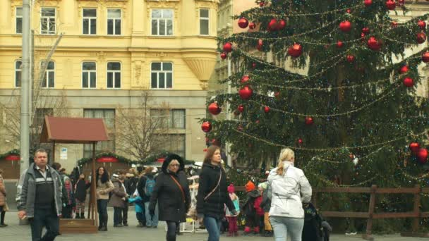 BRNO, CZECH REPUBLIC, DECEMBER 21, 2018: Christmas tree luminous and shines beautiful decorated with ornaments and flasks, children at wooden bell tower, joy of kindergarten bell ring