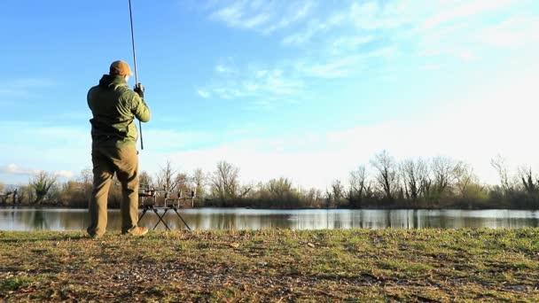Halász, csinál a ponty halászat egy napsütéses reggelen