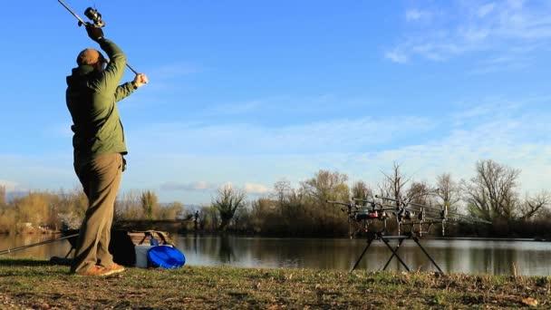 Rybář dělá kaprů na slunečné ráno v pomalém pohybu
