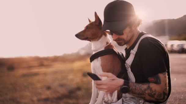 pohledný stylový muž s tetováním psa drží a procházení mobilní telefon venku