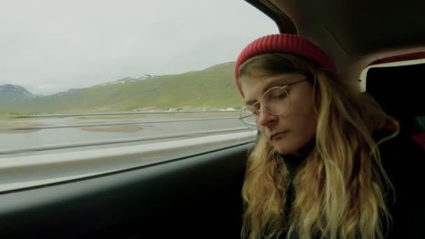 Mladá žena na roadtrip poslouchá hudbu