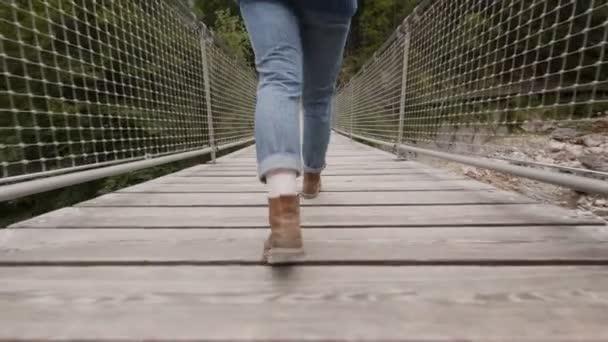 Žena v džínách a botách chodí na mostě