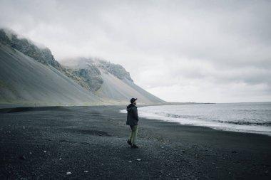 Lonely man walks on grey black volcanic sand beach